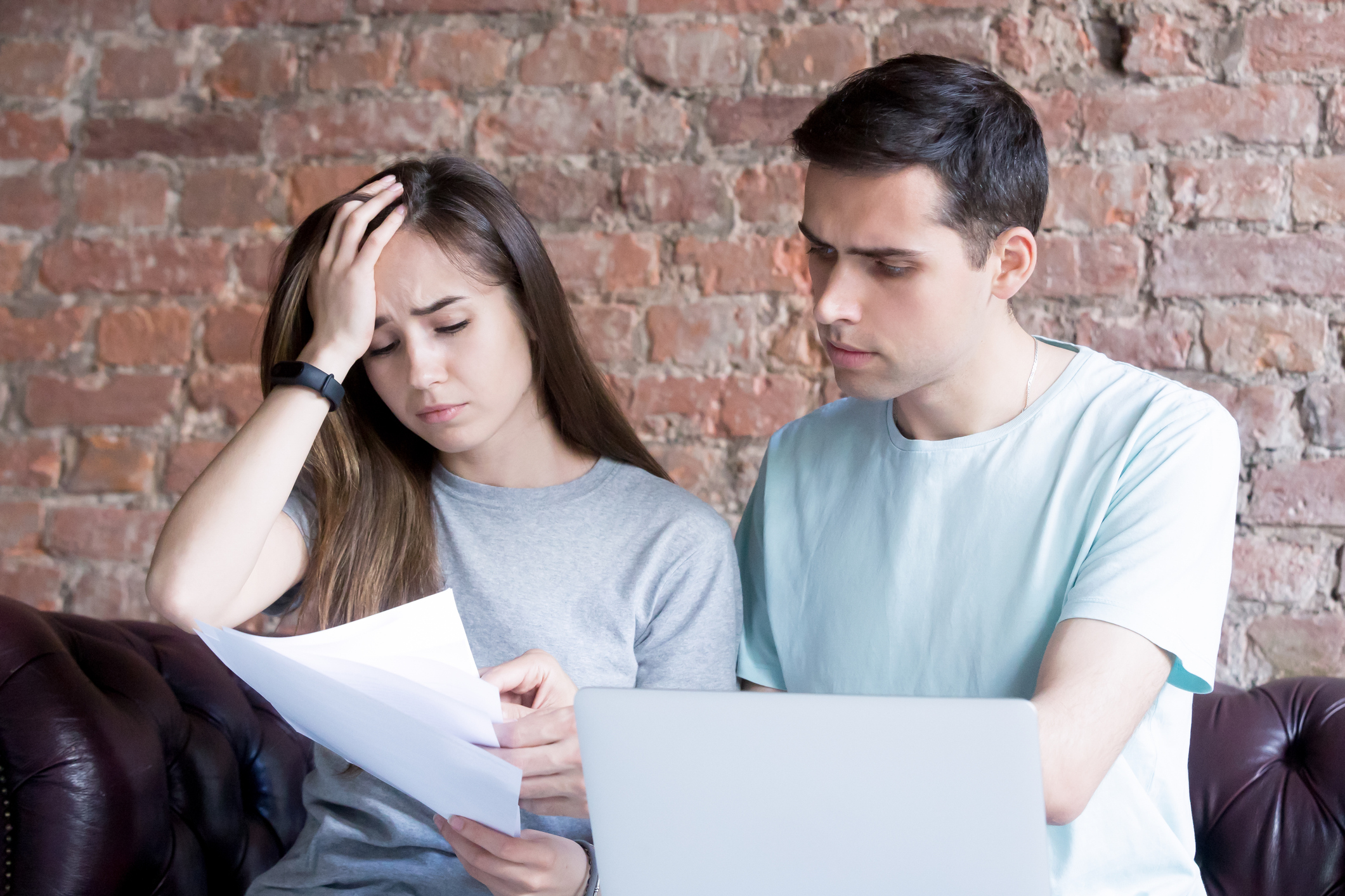 Distressed young couple reviewing paper work on sofa.