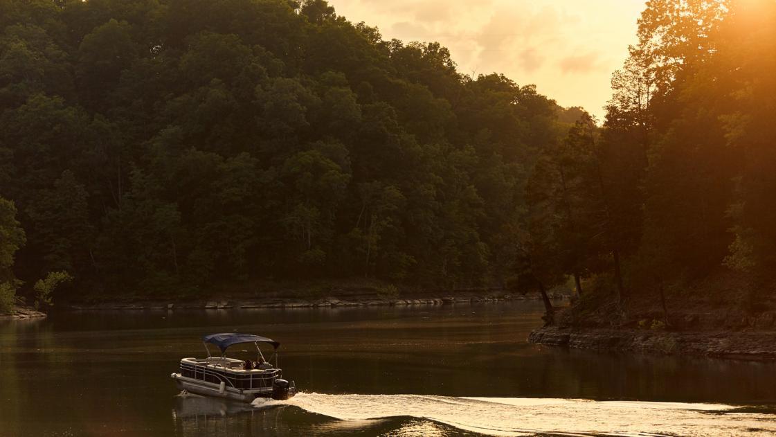 Pontoon boat on the lake at sunset.