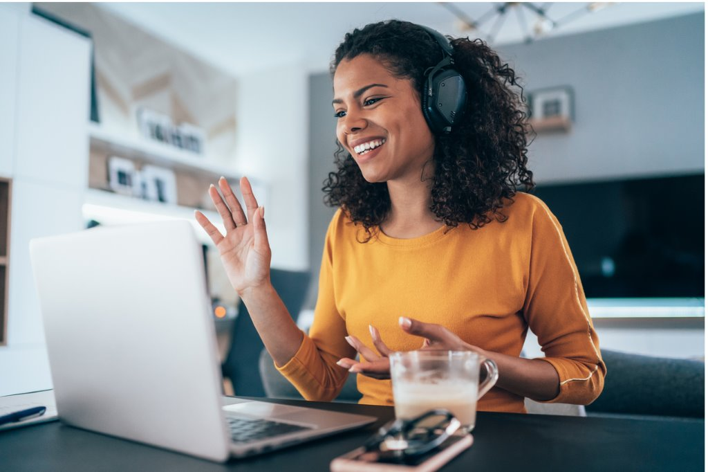 African american woman in headphone waves to video screen on laptop.