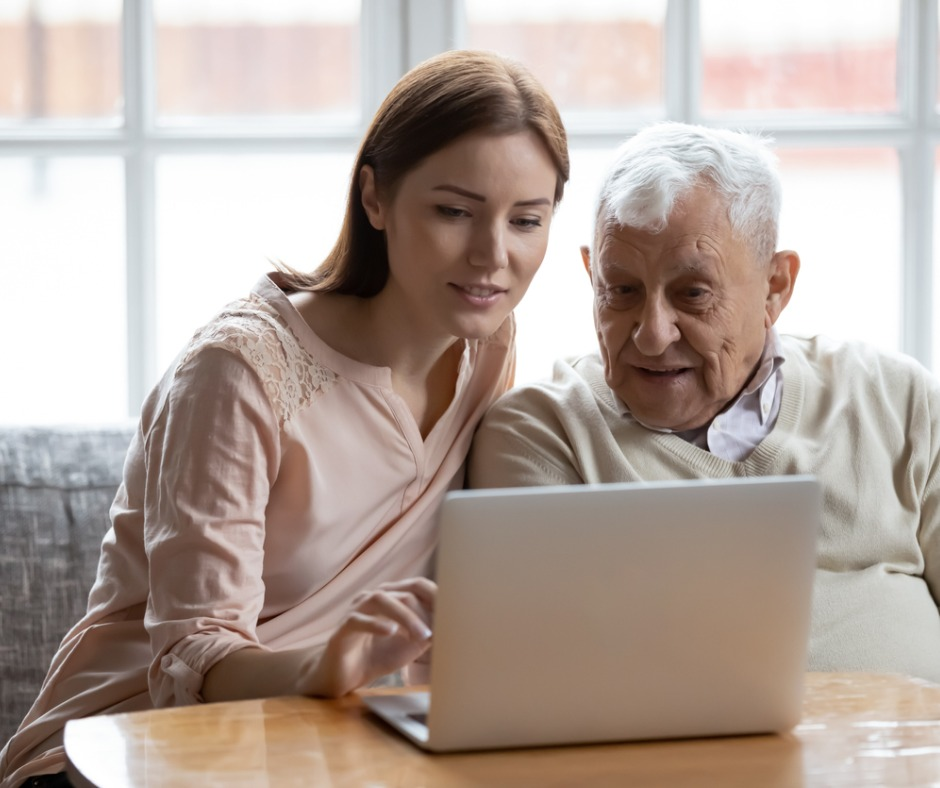 adult daughter helping older dad on laptop