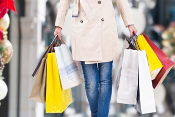 Woman with shopping bags holiday buget tips Banner