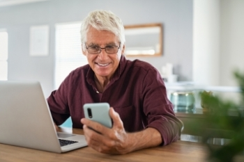 Older man viewing phone screen while sitting in front of laptop Banner