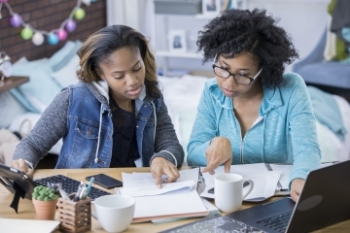 Mom and teen daughter reviewing financial documents Banner