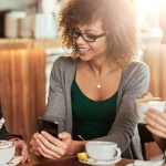 Woman drinking coffee with phone