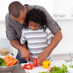African american father helping son cut vegetables.